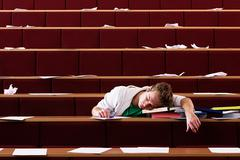 Student sleeping in lecture theatre - stock photo