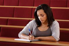 Female student in lecture theatre - stock photo
