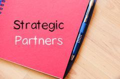Strategic partners write on notebook Stock Photos