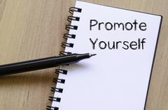 Promote yourself write on notebook - stock photo