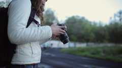 Young beautiful girl enjoys a digital SLR camera in the street Stock Footage