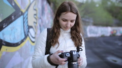 Girl - photographer adjusts the digital SLR camera Stock Footage