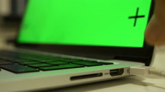 USB cable is connecting to a slot, hand is plugging cable into a laptop, chroma Stock Footage