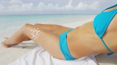 Sexy bikini body sunbathing on beach vacation with sun lotion drawing Stock Footage