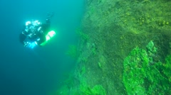 Tech diver swimming near the sheer cliff overgrown Baikal Demosponge Stock Footage
