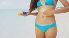 Beach suntan bikini woman applying sunscreen spf lotion on stomach - body crop Stock Footage