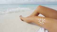 Suntan beach woman tanning legs in water with sun drawing in sunscreen lotion Stock Footage