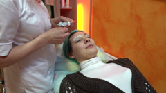 Beautician smears cream on the eyebrows - stock footage