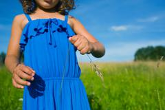 A girl holding a blade of grass - stock photo
