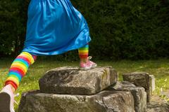 A girl stepping on rocks Stock Photos
