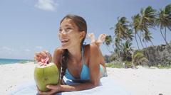 Happy bikini woman relaxing drinking fresh coconut water on beach vacation - stock footage