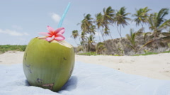 Green coconut served with straw on beach towel to drink fresh water on vacation - stock footage