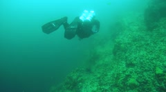 Technical diver loats next to a sheer cliff of lake Baikal Stock Footage