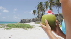 Fresh coconut water on Caribbean beach - vacation woman holding tropical fruit Stock Footage