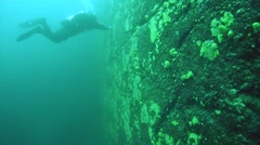 Technical diver loats next to a sheer cliff of lake Baikal - stock footage
