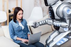 Modern robot giving cup of coffee to cheerless girl - stock photo