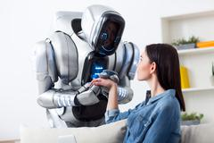 Robot holding hands of charming girl Stock Photos