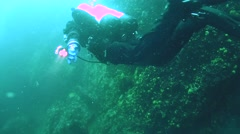 Tech diver swimming near the sheer cliff overgrown Baikal Demosponge - stock footage
