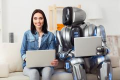 Pleasant girl sitting on the couch with robot Stock Photos