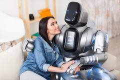 Positive girl and robot bonding to each other Stock Photos