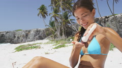 Beach bikini body woman applying sunscreen lotion relaxing on Caribbean vacation Stock Footage