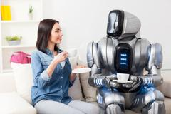 Positive girl resting on the couch with robot - stock photo