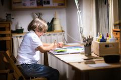 Little boy paiting in a dark room late in the evening Stock Photos