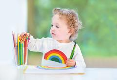 Sweet little baby girl with curly hair paiting with colorful pencils Stock Photos