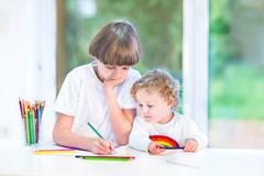 Brother and little toddler sister having fun together painting - stock photo