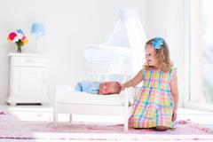 Little girl playing with newborn baby brother Stock Photos