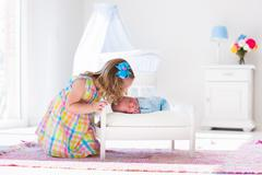 Little girl playing with newborn baby brother - stock photo