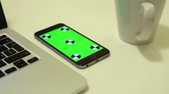 Smartphone lies on an office desk with chroma key on a screen - stock footage