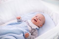 Baby boy in a crib under knitted blanket - stock photo