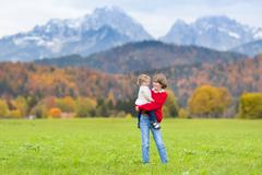 Two kids playing  in scenery with yellow trees and snow covered mountains Stock Photos