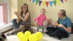 Dad playing with toy guitar and lovely baby girl dance have fun with her mom Stock Footage