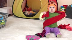 Awesome baby girl measure colorful knitted scarf and hat between toys in room. Stock Footage