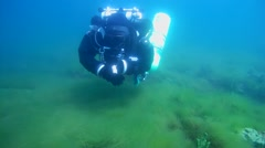 Tech diver floats abo e the bottom of newly-fallen snow bright green algae - stock footage