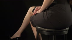 Elegant young woman in sexy short black bodycon dress sitting on stool Stock Footage