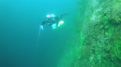 Tech diver swimming near the sheer cliff overgrown Baikal Demosponge Stock Footage