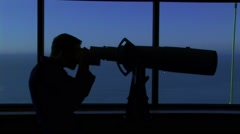 Man and telescope in silhouette - stock footage