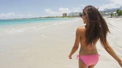 Bikini vacation woman relaxing walking on Isla Verde beach San Juan Puerto Rico Stock Footage