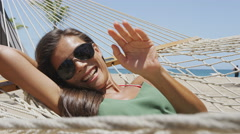 Happy sunglasses girl tanning relaxing in beach hammock saying hi waving hello Stock Footage
