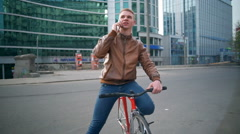 young male bicyclist talks on the phone in downtown slow motion - stock footage