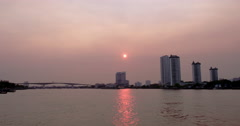 Sunset on river in Bangkok with bridge and apartment towers in background Stock Footage