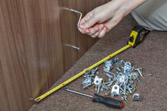Self-assembly furniture, hand with an Allen key tighten screw. Stock Photos