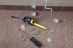 Metal fittings, clamps and hand tools for installing furniture. Stock Photos