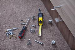 Steel fasteners, brackets and hand tools to install furniture. Stock Photos