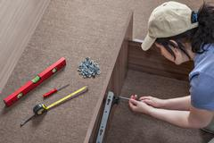 Woman assembles furniture, hinges lifting mechanism screwed to bed frame. Stock Photos