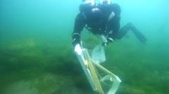 Underwater painter Yuriy Alekseev preparing to paint under water Stock Footage