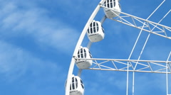 Rotating Ferris wheel against the blue sky and clouds - stock footage